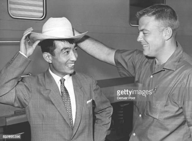 Clifford Latimer helps friend Lonnie Takeshita try on cowboy hat Credit Denver Post