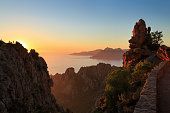 Golden sunset over coastal cliffs. At Calanche de Piana and the Golf of Porto, Corsica, France.