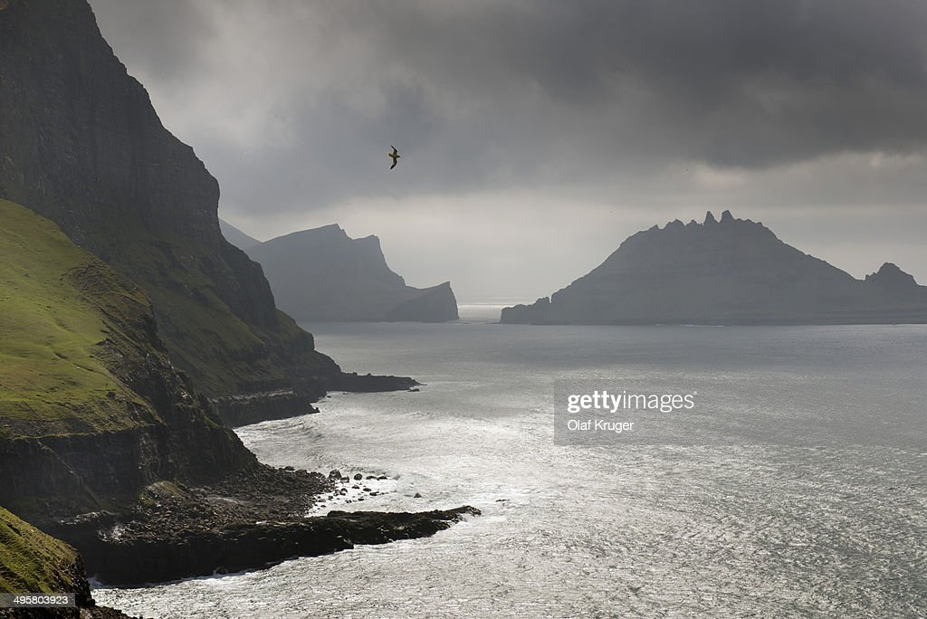 Cliffs in front of the silhouette of the rugged rocks of Tindholmur, Vagar, Faroe Islands, Denmark