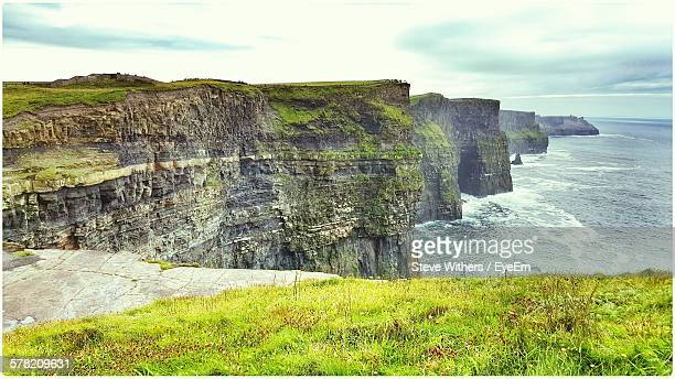 Cliffs Of Moher By Sea Against Cloudy Sky