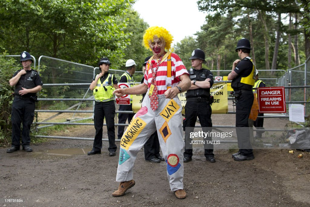 A climate and anti-fracking protestor dressed as a clown dances outside the gates to a drill site operated by Cuadrilla Resources Ltd in Balcombe in southern England, on August 18, 2013. British energy firm Cuadrilla scaled back its operations at a rural site in southern England as more than 1,000 protesters prepare a six-day 'action camp' in protest against fracking.