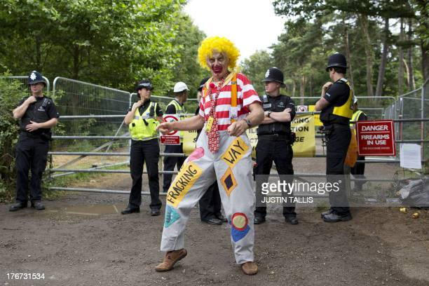 A climate and antifracking protestor dressed as a clown dances outside the gates to a drill site operated by Cuadrilla Resources Ltd in Balcombe in...