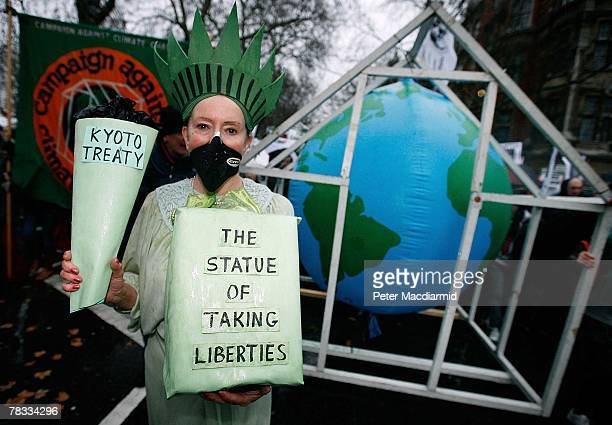 A climate change protestor dressed as The Statue of Liberty marches near Parliament on December 8 2007 in London Demonstrators are gathering in more...