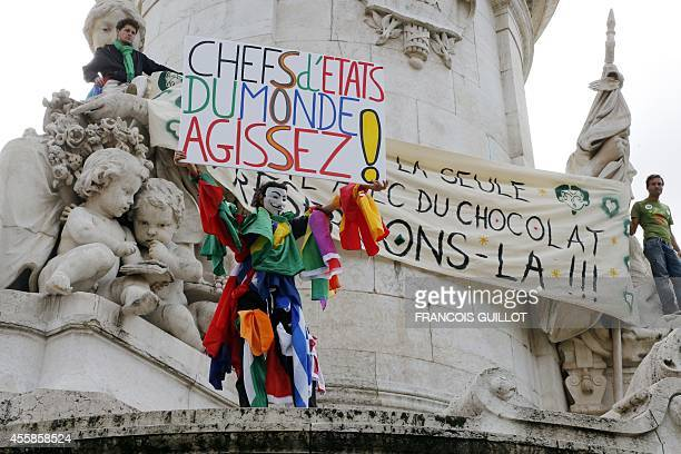 A climate protester wearing a Guy Fawkes mask holds a banner reading ' World leaders act' on the Republique's statue during a demonstration to fight...