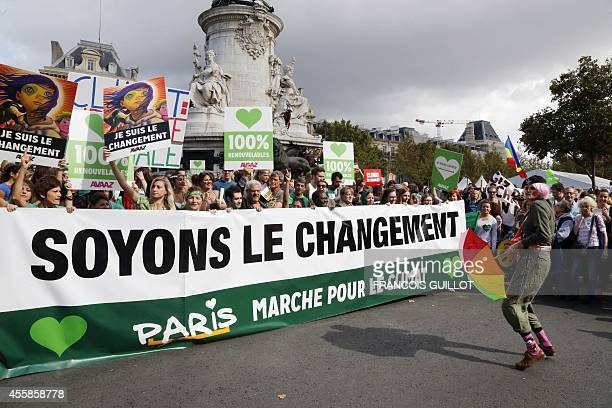 Climate protesters hold a banner reading ' Let's be the change' on the Republique's square during a demonstration to fight climate change on...