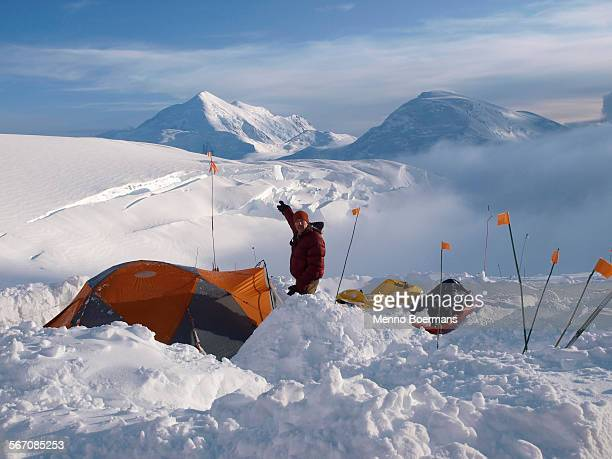 Climber and ranger is standing next to his tent and pointing to Mount Foraker from 12.000 feet camp high on Mount McKinley.