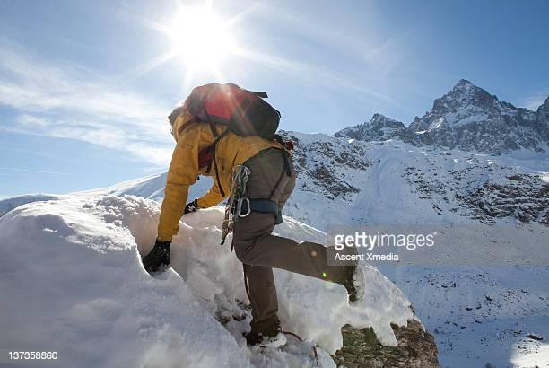 Climber ascends through deep snow to summit