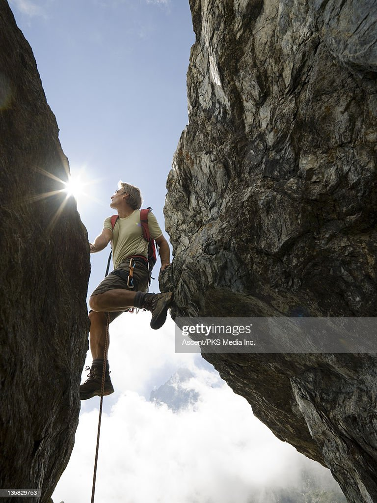 Climber ascends through gap between rocks, mtns : Stock Photo