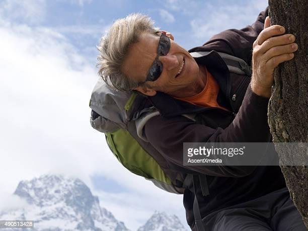 Climber checks holds while climbing rock ridge