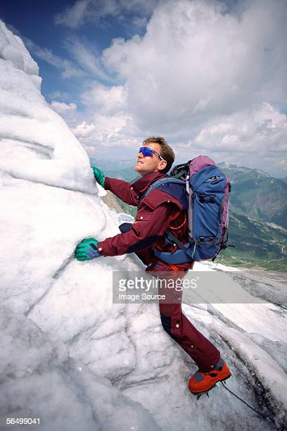A climber climbing on a rock covered in ice