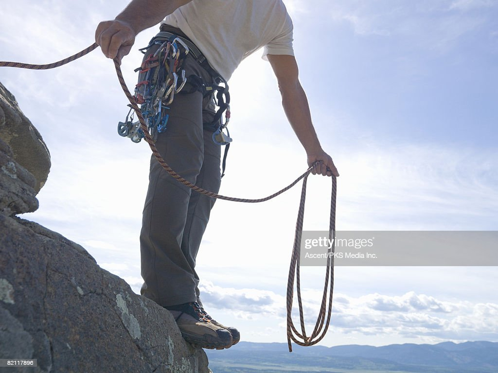 Climber coiling rope at edge of cliff : Stock Photo