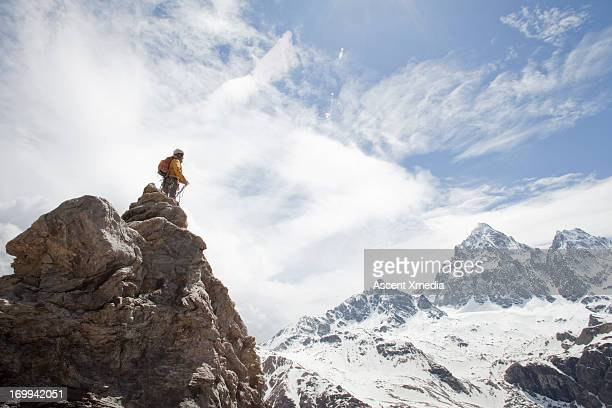 Climber coils rope on rock summit, looks to mtns