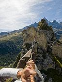 Climber crosses gap on rope traverse, ridgeline