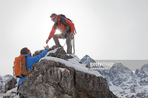 Climber extends helping hand to teammate, mtns