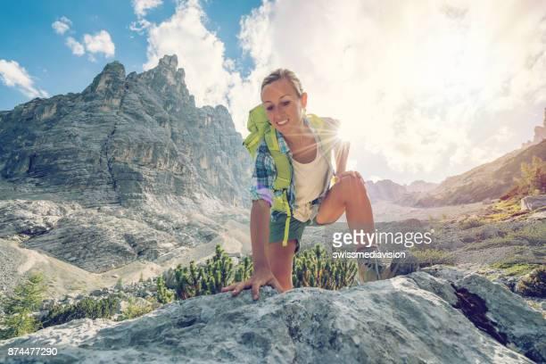 Climber female reaching mountain top, Dolomites, Italy