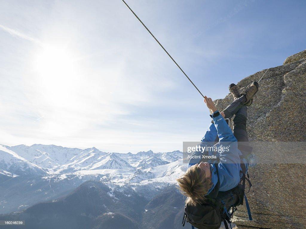 Climber follows Tyrolean travse above mountains : Stock Photo