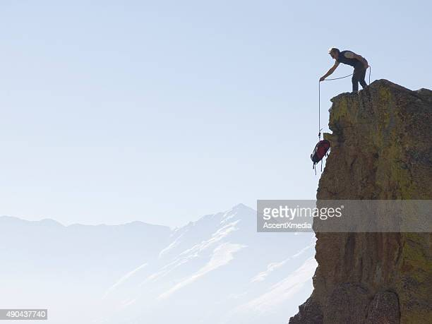 Climber hauls backpack up steep rock face, above mountains