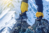 Climber in crampons stands on the rocks in front of the entrance to the peak on the background of the snowy mountains. Feet close up. The concept of the travel path and achieving the goal