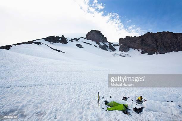A climber melts snow near his campsite where two bivy sacks are set up.