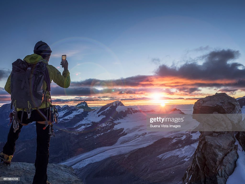Climber on a peak photographing sunrise with smart