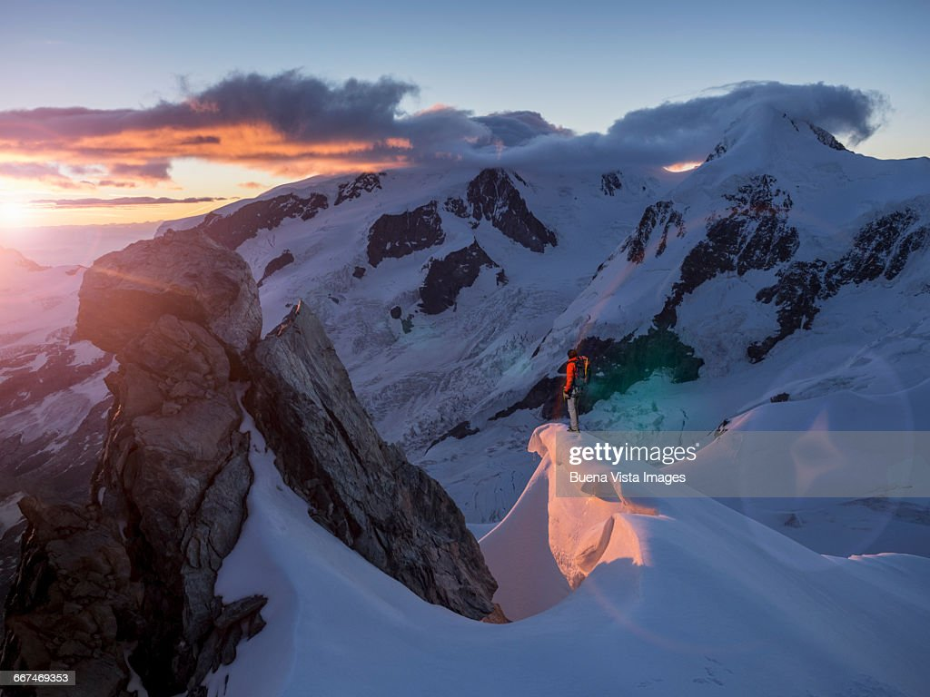 Climber on a peak watching sunrise