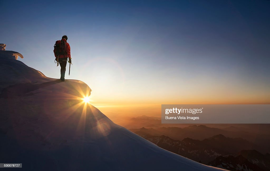 Climber on a snowy range at sunset : Stock Photo