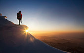 Climber on a snowy range at sunset