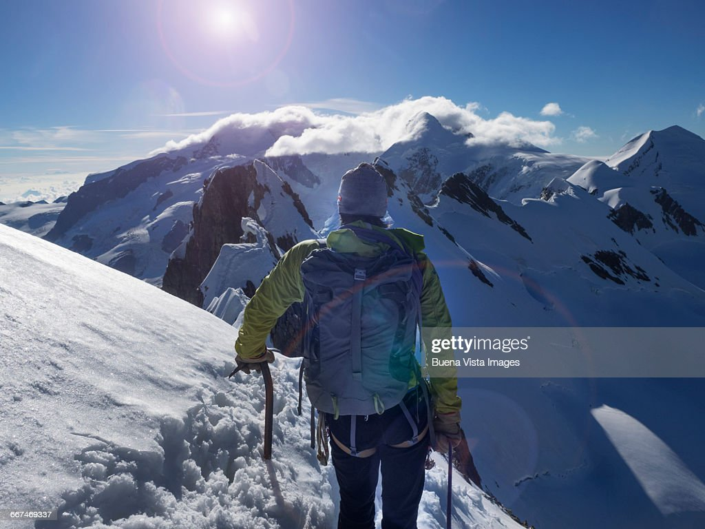 Climber on a snowy ridge watching sunrise