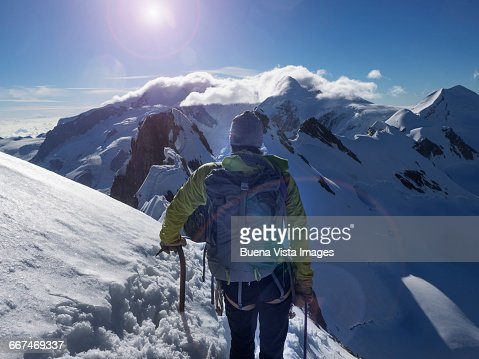 Climber on a snowy ridge watching sunrise