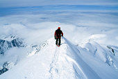 Climber on steep summit of mountain in snow.