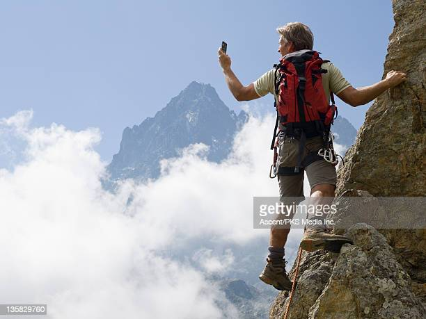 Climber pauses on cliff edge, takes picture of mtn