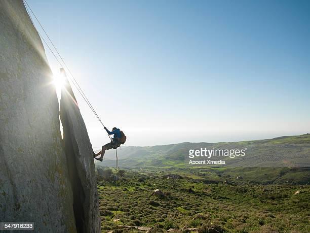 Climber rappels (abseils) from ridge crest