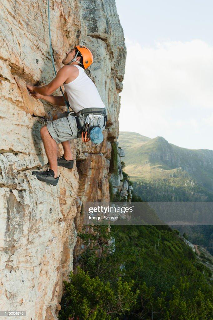 Climber scaling steep rock face : Stock Photo