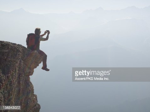 Climber sits on edge of overhang, takes picture : Stock Photo
