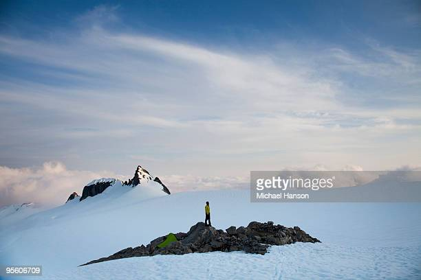 A climber stands on a rock outcrop in the middle of a glacier while climbing in the North Cascades,