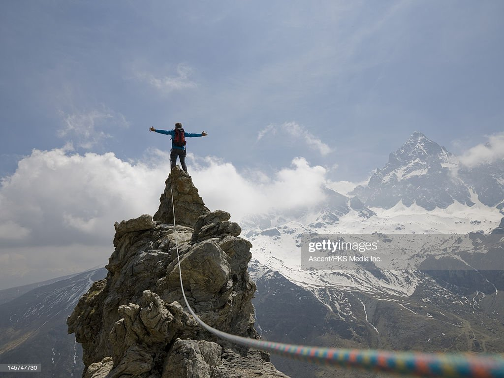 Climber stands on summit of pinnacle, arms out : Stock Photo