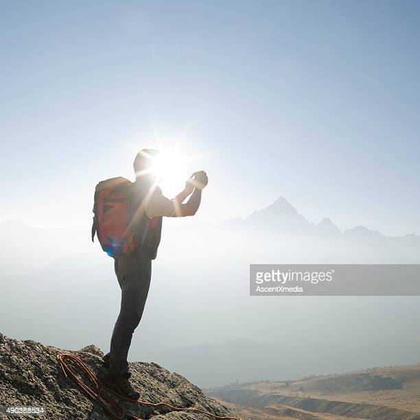 Climber stands taking picture on mountain summit