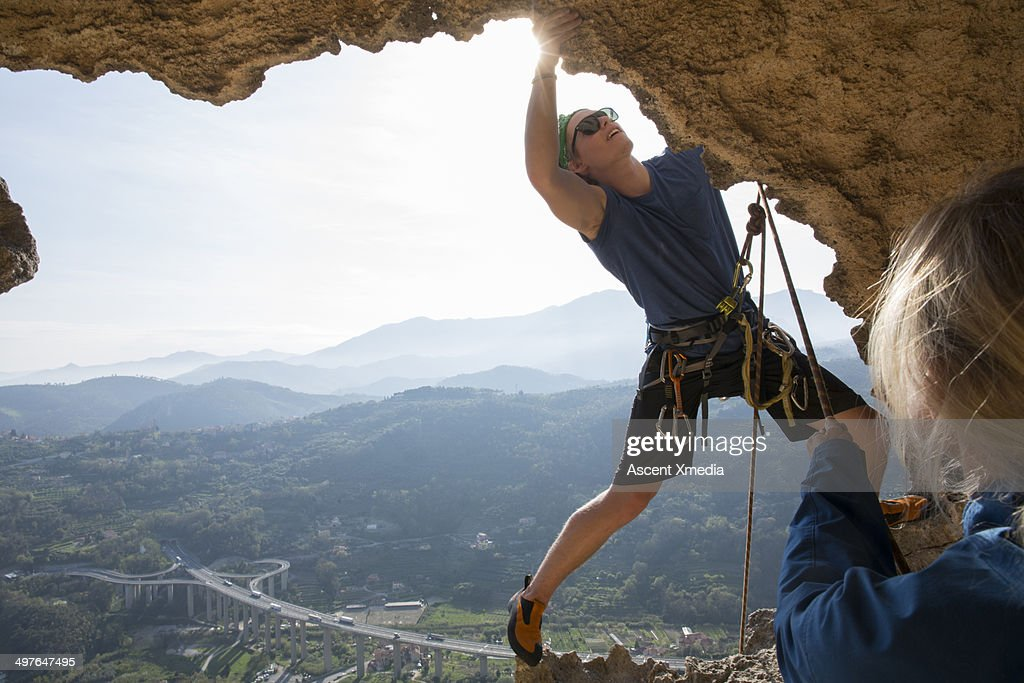 Climber stretches for hold on cave edge, hwy below