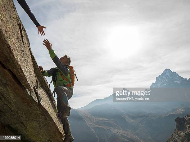 Climber stretches hand towards that of teammate