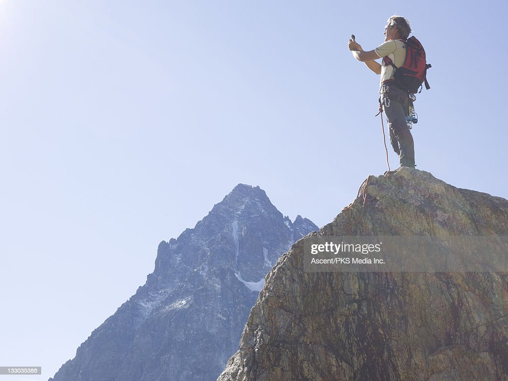 Climber takes picture from mountain summit : Stock Photo