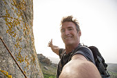 Climber takes selfie form mountain wall, above sea