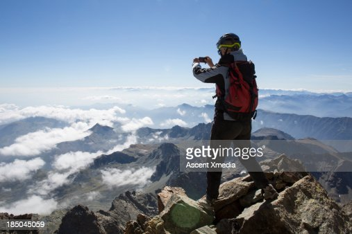 Climber takes smart phone pic from mountain summit : Stock Photo