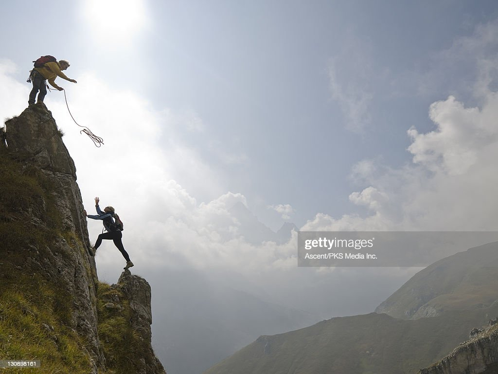 Climber throws rope to partner below, above mtns : Stock Photo