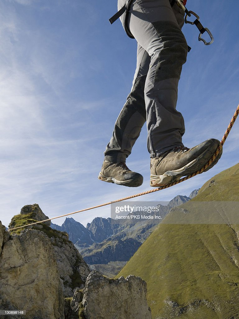 Climber traverses rope stretched over mtns, valley : Stock Photo