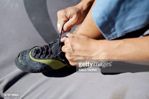Climber tying climbing shoe