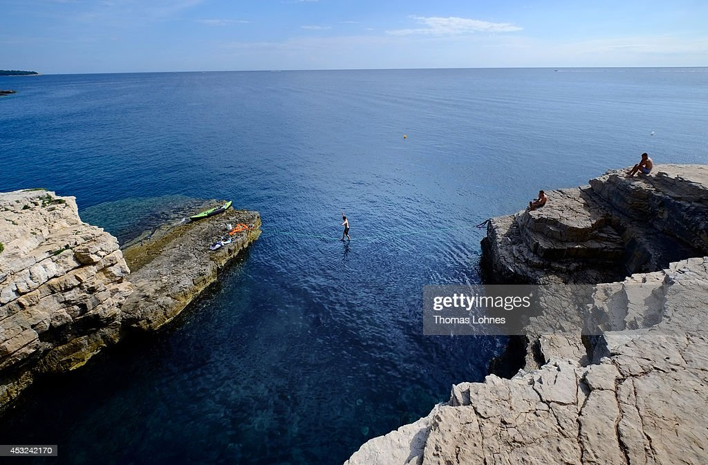 A climber walks over a 'Slackline' at the cliffs of Stoja on August 5, 2014 near Pula, Croatia. The area is known for 'Deep Water Soloing' (DWS), free climbing over water, is a relatively new discipline and is popular with climbers wanting to go rock climbing during the high summer temperatures. Climbing over deep water means most of the climbing routes are safe for beginners but still offer a challenge for the more advanced climber. There are many opportunities for DWS along the mile-long cliffs of Croatia.