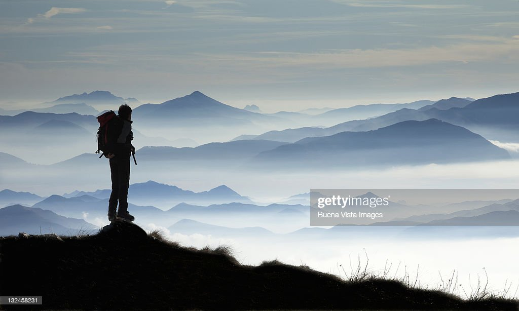 Climber watching mountains in the mist : Stock Photo