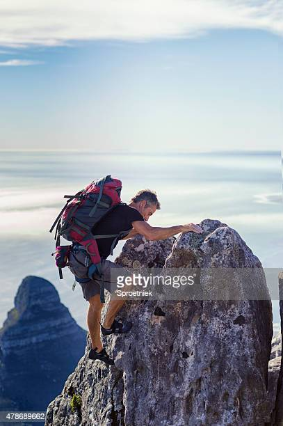 Climber with backpack reaches top of rock