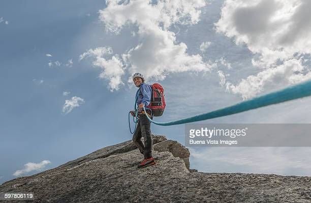 A climber with rope on a mountain top