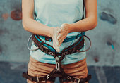 Climber woman coating her hands in powder chalk magnesium and preparing to climb indoor, close-up